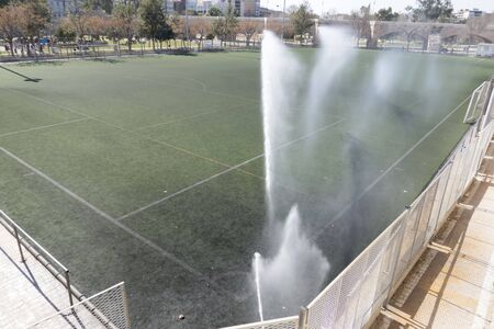 artificial grass soccer field watered with sprinklers