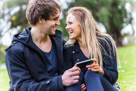 togheter: Young attractive couple enjoying their time togheter using a smartphone. Relationship and technology concept Stock Photo