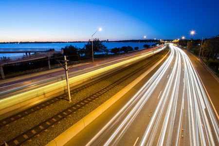 blurred lights: Long time exposure on a highway and railway with running car light trails