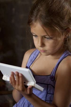 concentrating: Young Girl concentrating on handheld game console Stock Photo
