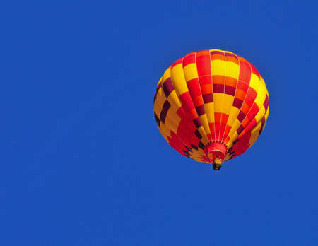Colorful hot air balloon flying in a clear blue sky photo