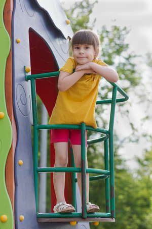 6 years old girl standing on the balcony of a toy house