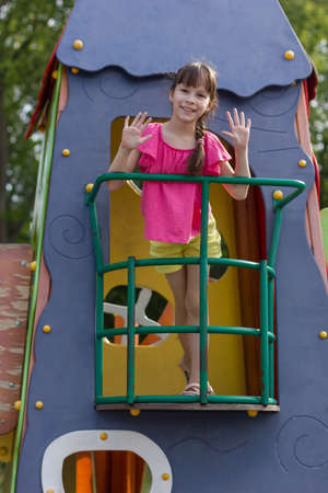 Adorable girl waves her hands on the balcony of a toy house