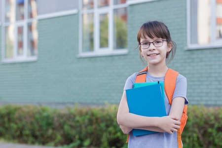 Happy girl with backpack and notebooks going to school. Reklamní fotografie