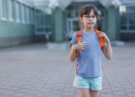 Cute happy schoolgirl with backpack leaving school Reklamní fotografie