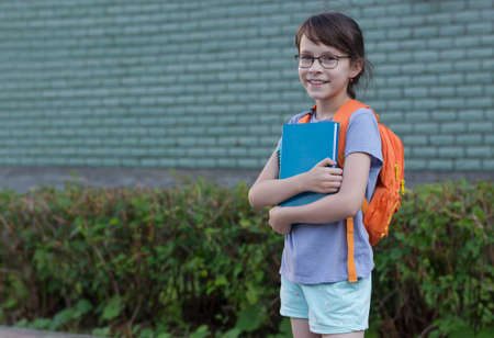 Happy girl with backpack and books going to school. Education and study. Knowledge day. Reklamní fotografie