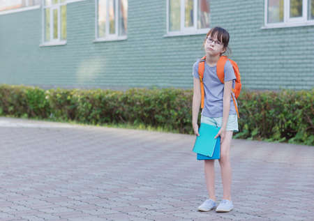 Sad schoolgirl back to school. Portrait of tired child with backpack and notebook