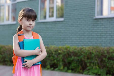 Little schoolgirl with backpack holding notebooks