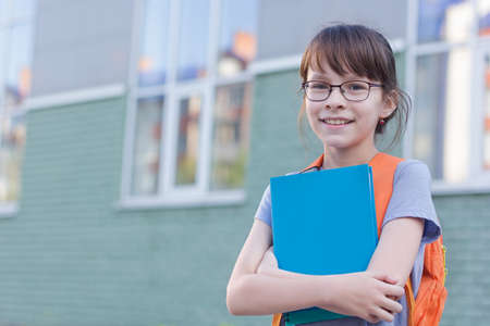 Portrait of cute smiling schoolgirl with glasses isolated on a school green wall