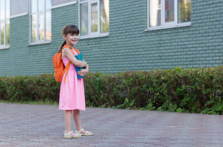 Portrait of little school girl child with backpack and notebooks isolated on a school background Reklamní fotografie