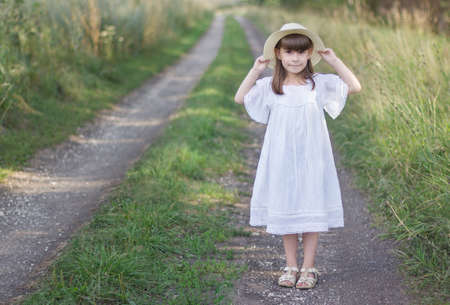 Beautiful girl in a hat stands on a road near field of rye. Little girl holds on to her hat Reklamní fotografie