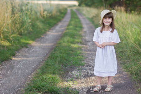 Happy little girl on the road. Cute girl in a white dress stands near a field with spikelets of wheat.