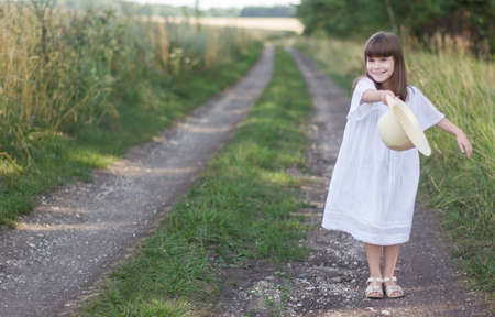 Little girl plays with her hat on a road near field of rye.