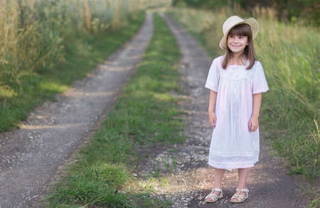 Little girl in a hat and white dress stands on a road near field of rye. Reklamní fotografie