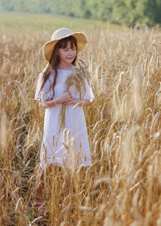 Beautiful girl in a hat stands on a field of rye at sunset.