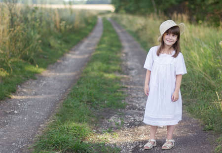 Happy little girl in a hat and white dress stands on a road near field of rye.