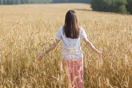 summer holidays, vacation and people concept - happy young girl in white dress on cereal field