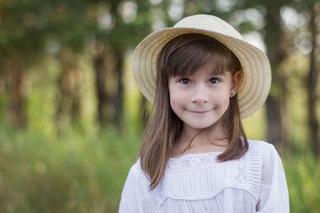 Cute smiling girl in a white dress stands near field Reklamní fotografie