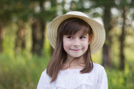 Happy little girl on the forest. Cute smiling girl in a white dress looks away