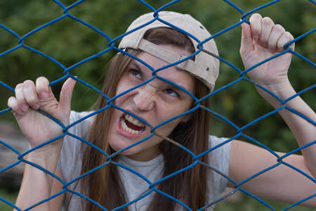 creepy zombie woman screams and climbs the iron net Reklamní fotografie