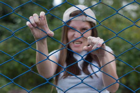 creepy zombie screams and climbs the iron net