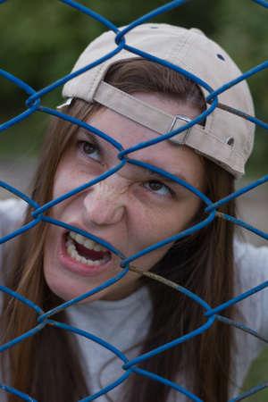 creepy zombie in cap looks away throught the iron net Reklamní fotografie