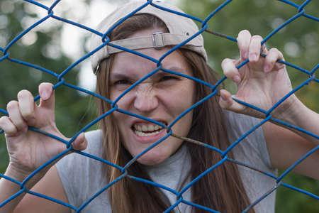 creepy zombie in cap looks throught the iron net
