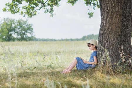 Cute girl enjoy reading book under the tree. Little girl is feeling relax in beautiful summer day. Reklamní fotografie
