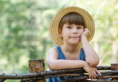 Portrait of cute little girl in the forest. Adorable toddler in a hat is leaning on a wooden fence Reklamní fotografie