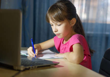 Distance learning online education. A schoolgirl studies at home and does homework by internet