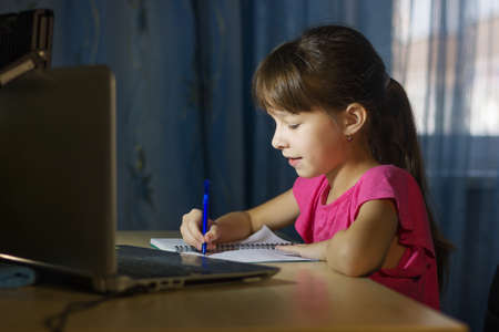 Distance learning online education. A schoolgirl studies at home and writes homework