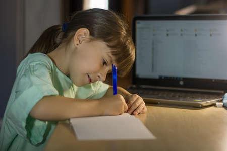 Distance online education. Little schoolgirl studies at home. Reklamní fotografie