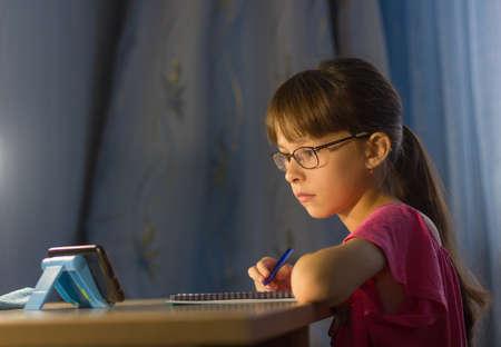 Distance online education. Adorable schoolgirl looks at cellphone Reklamní fotografie