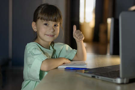 Distance learning education. Happy girl learn english language online with laptop at home. Little girl shows a like