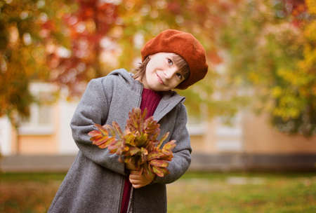Adorable girl in red hat smiles. The child holds leaves at the autumn park.