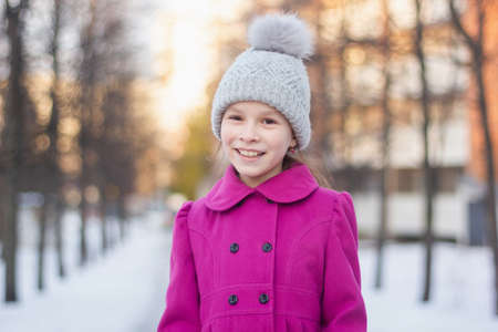Happy young girl having fun in a winter park. Winter holidays concept. Girl outdoors. Gilr wearing pink coat and knitted hat walking on a beautiful day.