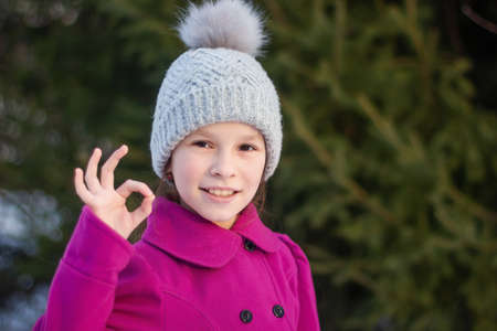 Smiling beautiful young girl in pink coat shows ok, against green of winter park.