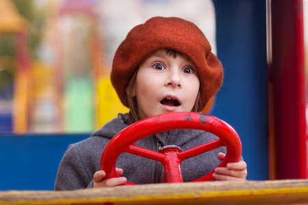 Photo of amazed girl in red cap keeping red steering wheel on a playground. Close up portrait of little girl opening mouth and looks away.