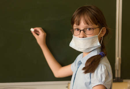 Adorable student in mask is writing on the chalkboard in classroom. Close-up portrait of little girl holding a piece of chalk during Covid-19 pandemic