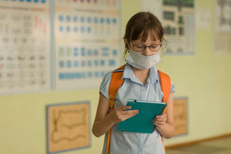 Schoolgirl with face mask went back to school after covid-19 quarantine and lockdown. The child read text in a notebook at school hall