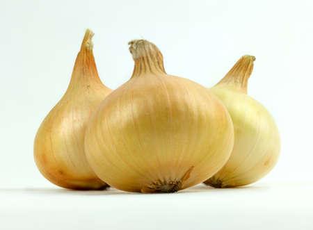 Three yellow organic onions on white background. Reklamní fotografie