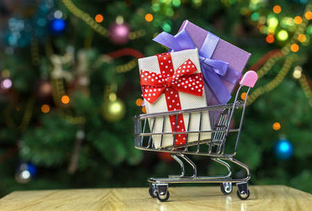 Grocery shopping cart with wrapped holiday gift boxes inside. Christmas family shopping concept Reklamní fotografie