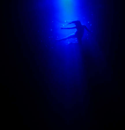 assassinate: Woman floating in the deep blue ocean, she looks like swimming or flying or dancing in the water, an ocean, the sea, a pool. She may have been murdered, she looks like dead Stock Photo
