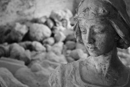 meditative: A monochrome plaster statue in a sculptor's studio in Volterra, Italy. The statue looks like meditating about her origin, the stone.