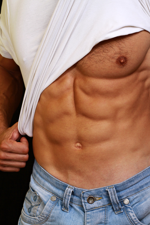 bStrong athletic guy in jeans showing his abs. b