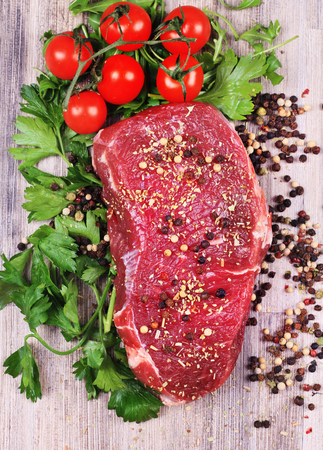 beefsteak: Raw beefsteak with spices and cherry tomatoes on wooden background Stock Photo