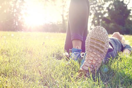 descansando: Atleta femenina descansar y relajarse despu�s del entrenamiento. Mujer que se acuesta en la hierba. Estilo de vida saludable y concepto de la felicidad