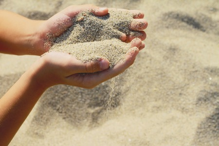 sand: Close up onChilds hands holding sand.summer beach holiday vacation concept