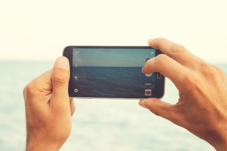 cell: Close up on male hands taking photo of sea coast with mobile phone. Summer beach holiday vacation concept Stock Photo