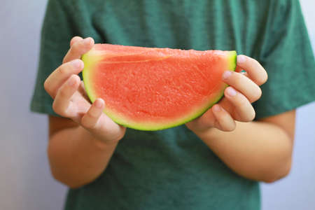 holding close: Close up on  Childs hands holding  watermelon. Selective focus image Stock Photo
